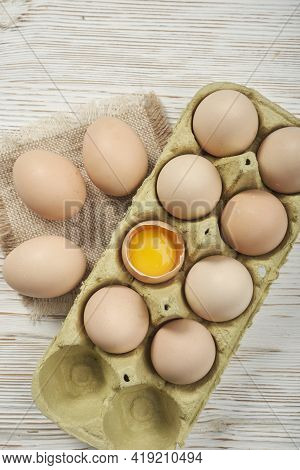 Close-up View Of Raw Chicken Eggs In Egg Box On Wooden Background. Raw Chicken Eggs In Egg Box Organ