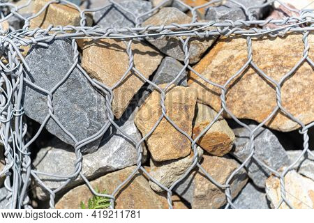 Close-up Of Brown Round Stones In A Grid. Large Stones Are Covered With Metal Mesh. Fencing Made Of