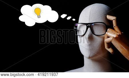Close Up Image Of Mannequin Wears Eyeglasses In Thinking Bright Idea Gesture With Light Bulb In Thin