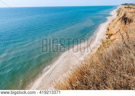 Coastal Clay Cliff And Sandy Beach . Craggy Coastline And Sunny Beach