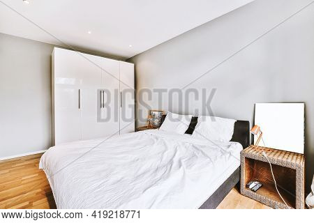 Comfortable Bed With Crumpled Duvet Located Near Bedside Tables With Lamps And Paintings Against Win