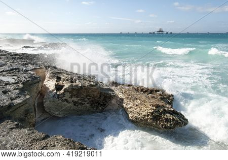 The View Of Waves Hitting Eroded Rocky Shore And A Wet Dock Installation In A Background On Grand Ba