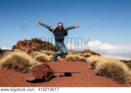 Happy Tourist In Full Growth In A Jump. The Traveler Jumps For Joy, Making A Gesture Of Victory. The
