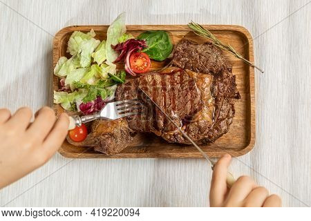 A Juicy Fresh Roasting Piece Of Steak On A Wooden Rectangular Dish Is Decorated With Fresh Salad And