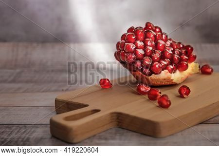 Close-up Of Peeled Pomegranate Wedges And Pomegranate Seeds On A Wooden Board In Sunlight. Dark Vint