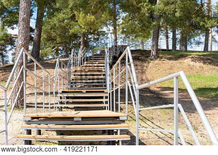 Wooden Staircase With Metal Railing In A Pine Forest On A Sunny Summer Day. Climb The Slope.