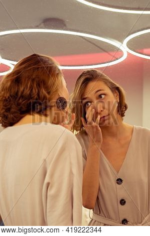 Young Woman Looking At Her Reflection In The Big Mirror.\nbeautiful Girl Taking Close Herself Look I
