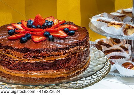 Chocolate And Dulce De Leche With Strawberry Cake, With Sweets On The Table