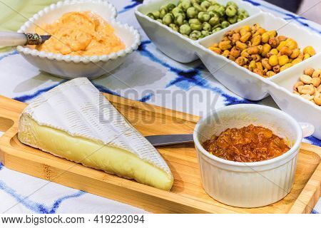 Brie Cheese With Apricot And Snacks On The Table For Tasting And Holiday Scenery