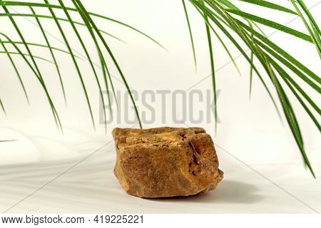 Natural Stone Podium With Palm Leaves On Neutral White Background. Concept Scene Stage Showcase For