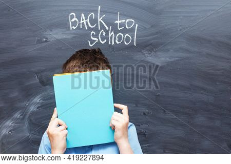 Child Boy Covered His Face With A Textbook Near A Chalkboard. Back To School Concept Background
