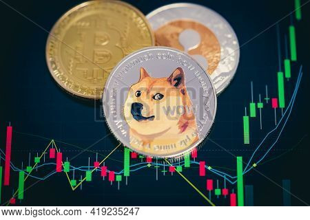 Dogecoin Cryptocurrency Silver Symbol And Stock Chart Candlestick On Tablets. With Capital Gain, Fun