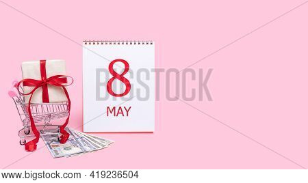 8th Day Of May. A Gift Box In A Shopping Trolley, Dollars And A Calendar With The Date Of 8 May On A