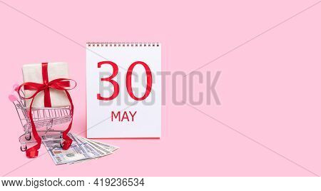30th Day Of May. A Gift Box In A Shopping Trolley, Dollars And A Calendar With The Date Of 30 May On