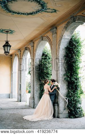 Bride With A Bouquet Of Flowers Embraces Groom Leaning Against An Arch Entwined With Green Ivy. Lake