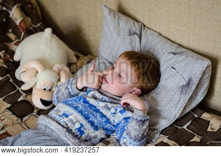 A 4-year-old Red-haired Boy Is Lying On The Bed And Picking His Nose With His Finger. Child Picking
