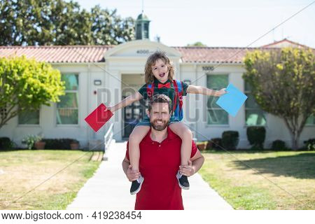 Father Piggyback Ride Supports And Motivates Son. Kids Education. Kid Going To Primary School.