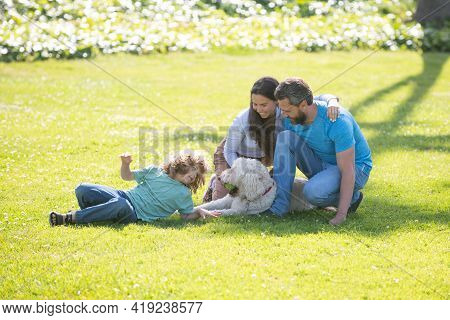 Beautiful Happy Family Is Having Fun With Dog Outdoors. Cute Family Portrait. The Concept Of A Happy