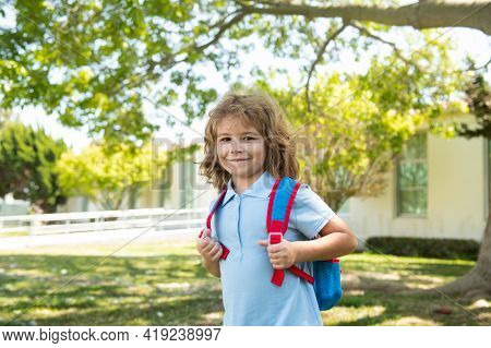 Kid With Backpack Going To School. Kids Education Concept. Child With Rucksacks Standing In The Park