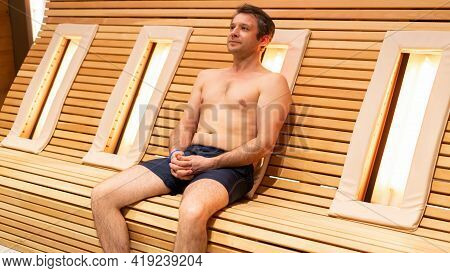 A Beefy Adult Man Warms His Back On A Wooden Slatted Bench With Infrared Heating Lamps In A Spa Well