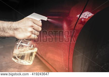 The Human Hand Was Spraying Chemical Liquid Onto The Car Body With A Water Spray Bottle