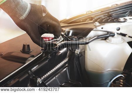 Mechanic Hand Is Opening The Radiator Cap To Check The Coolant Level Of The Car Radiator