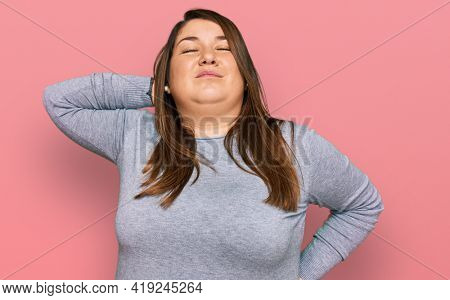 Beautiful brunette plus size woman wearing casual clothes suffering of neck ache injury, touching neck with hand, muscular pain