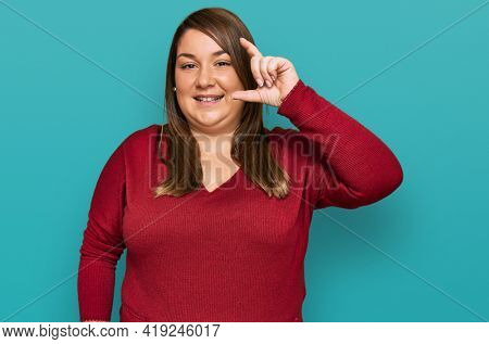 Beautiful brunette plus size woman wearing casual clothes smiling and confident gesturing with hand doing small size sign with fingers looking and the camera. measure concept.