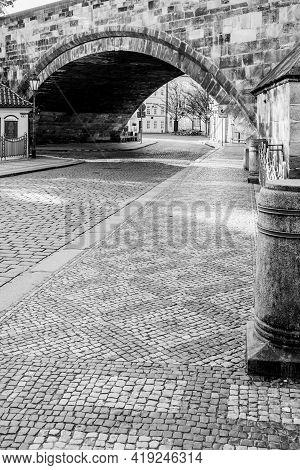 Old Cobbled Street Under The Charles Bridge, Czech: Karluv Most, In Prague, Czech Republic. Black An