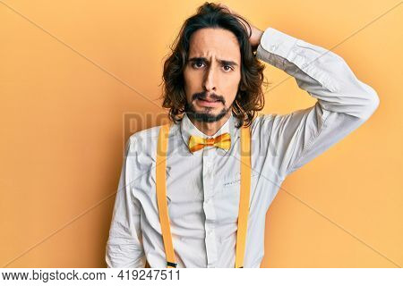 Young hispanic man wearing hipster elegant look confuse and wonder about question. uncertain with doubt, thinking with hand on head. pensive concept.