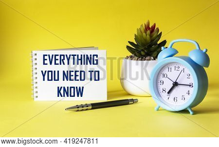 Everything You Need To Know. Motivational Quote Is Written On A Notebook, Next To A Cactus, An Alarm