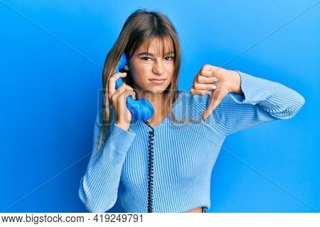 Teenager caucasian girl speaking on vintage telephone with angry face, negative sign showing dislike with thumbs down, rejection concept