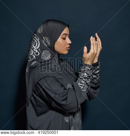 Young Arabian Woman In Hijab With Closed Eyes And Palms In Front Of Face Posing Sideways On Dark Blu