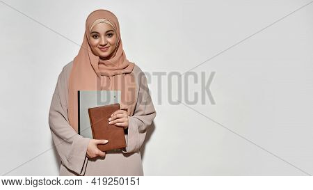 Happy Young Arabian Girl Student In Hijab With Notepad Smiling At Camera While Posing On Light Backg