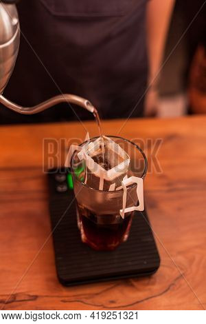 Freshly Brewed Glass Of Coffee With Pour Over Method With Paper Dripping Bag. Barista Brew Drink In