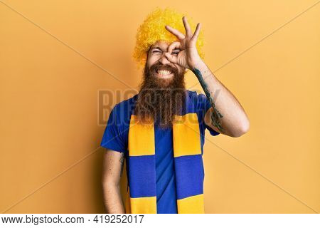 Redhead man with long beard football hooligan cheering game wearing funny wig doing ok gesture with hand smiling, eye looking through fingers with happy face.
