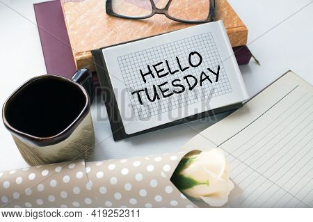 Office Table With Supply Notepad With Text Hello Tuesday Flower And Coffe Cup. Can Be Use As Concept