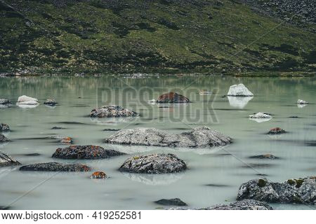Scenic Alpine Landscape With Rainy Circles Among Stones With Mosses And Lichens In Green Water Surfa