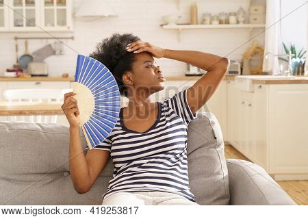 African Woman Suffer From Heatstroke At Home Use Paper Fan For Fresh Air. Overwhelmed Black Millenni