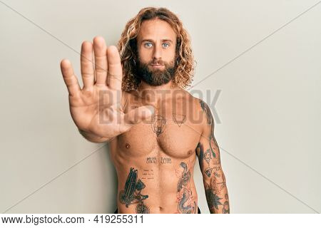 Handsome man with beard and long hair standing shirtless showing tattoos doing stop sing with palm of the hand. warning expression with negative and serious gesture on the face.