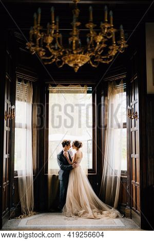 Groom Almost Kisses Bride Against The Background Of The Large Windows Of The Old Villa. View From Th