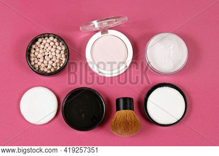 Makeup Setting Powders And Highlights Used On Face With Make-up Brush On Pink Background
