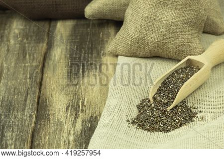 Nutritious Chia Seeds In A Wooden Spoon On A Wooden Background. Background With Space For Text