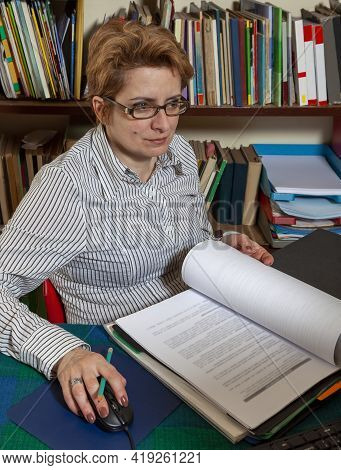 Image Of A Busy Woman Teleworking At Her Desk At The Home. Working At Home Became An Important Recom