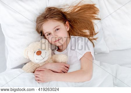 Little beautiful girl lying in the bed hugging teddy bear and smiling. Preteen child resting and holding toy. Home portrait of pretty female kid looking at the camera