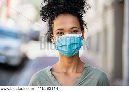 Portrait of happy african woman looking at camera with surgical mask due to covid-19. Close up face of beautiful black girl wearing protective face mask against the spread of coronavirus disease.