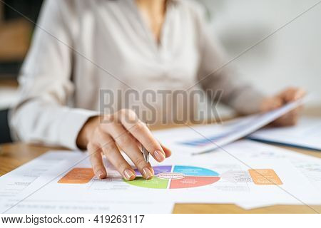 Businesswoman working at her desk in the office checking and analysing report. Young businesswoman reading charts and graphs at desk. Busy business woman working on reports and statistics graphs.