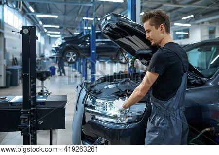 Male mechanic adjusts the headlights, car service