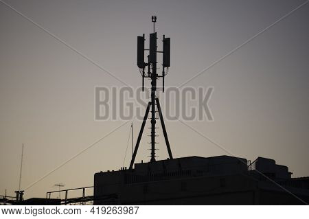 Cellular Transmitters On Top Of Building With A Blue Sky Morning