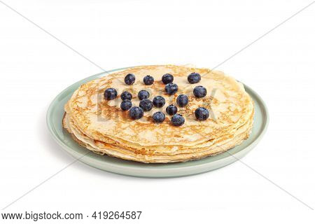 Pancake On Green Plate On White Background. Many Pancakes Are Stacked. Thin Pancakes With Crispy Cru